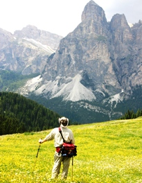 Hiker in field of wildflowers in the Dolomites