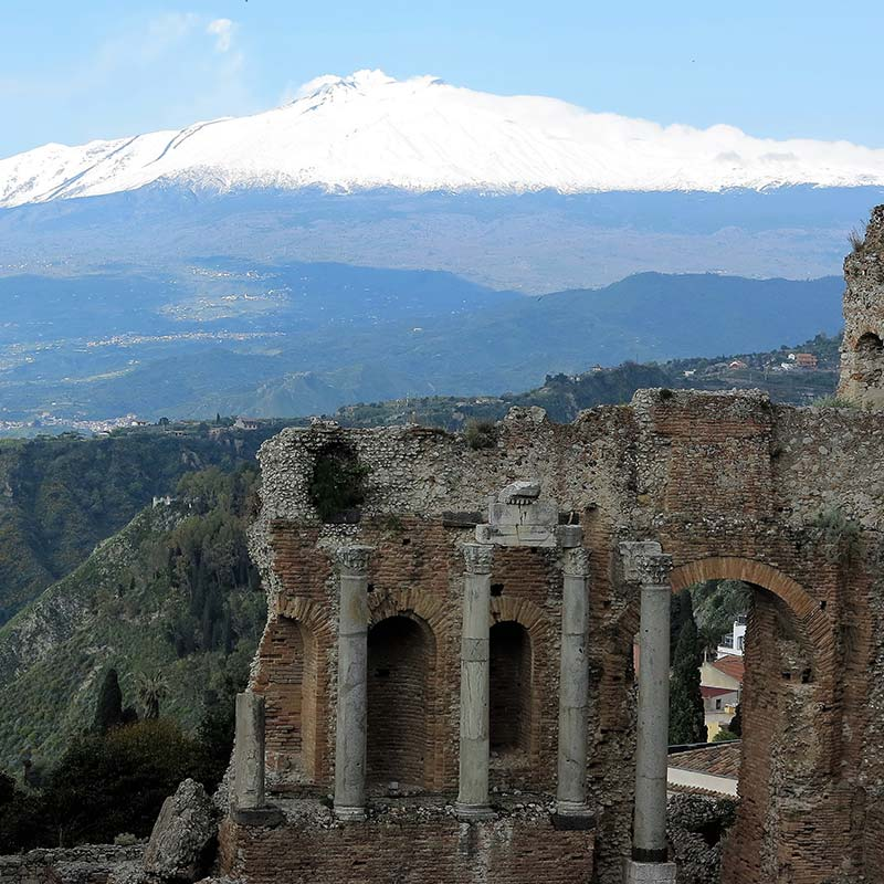 Greek theatre in Taormina with Mt. Etna volcano in background