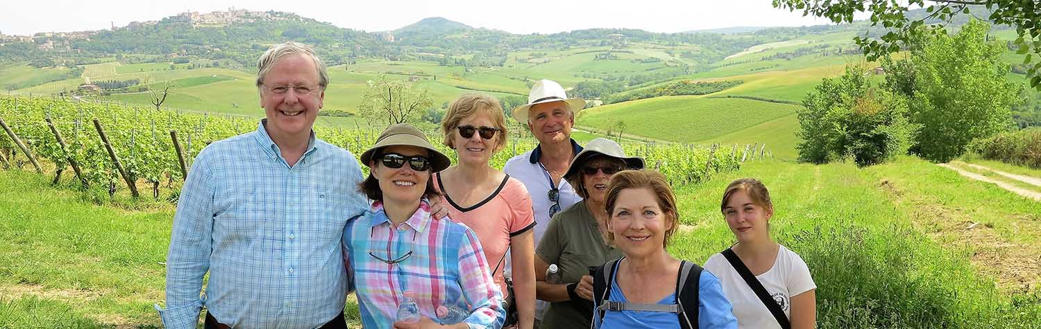 smiling tourists in front of lush, Italy landscape