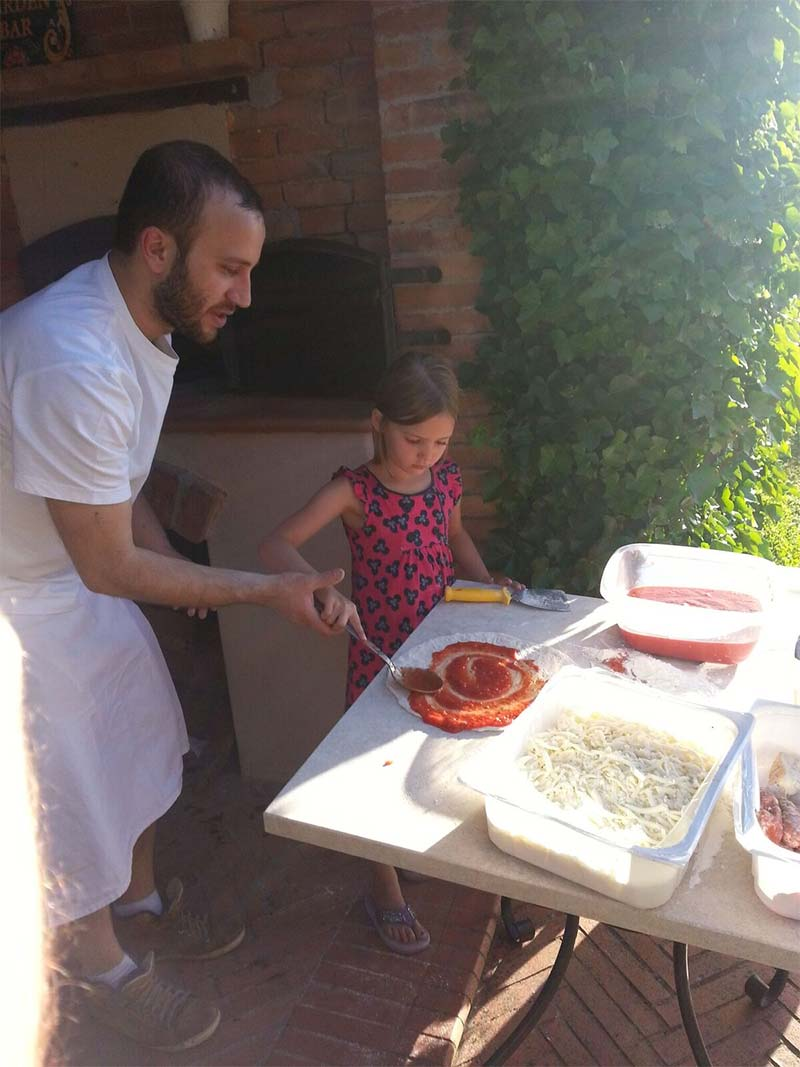 Chef helping child make pizza