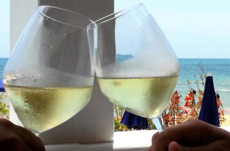 Glasses of white wine by the sea