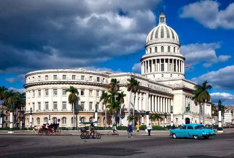 town in Cuba with buildings, pedestrians & cars