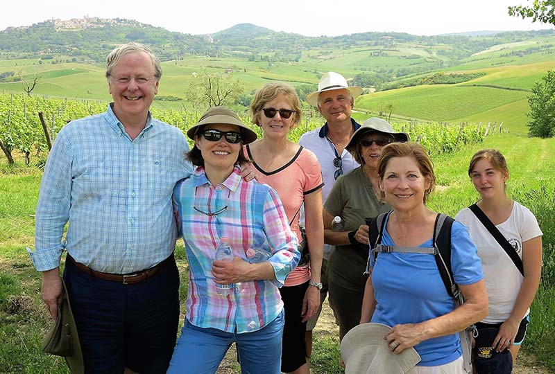 group of tourists standing in front of Italy countryside