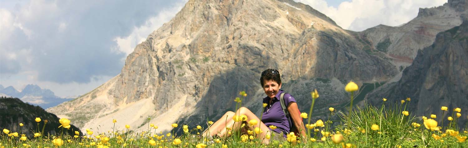 Woman resting in filed of wildflowers in the Dolomites