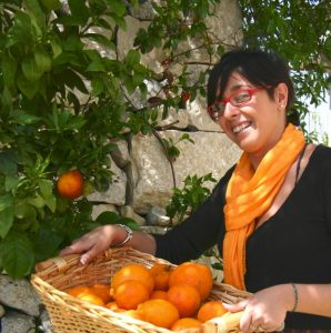 Lady with basket of fresh oranges in Sicily
